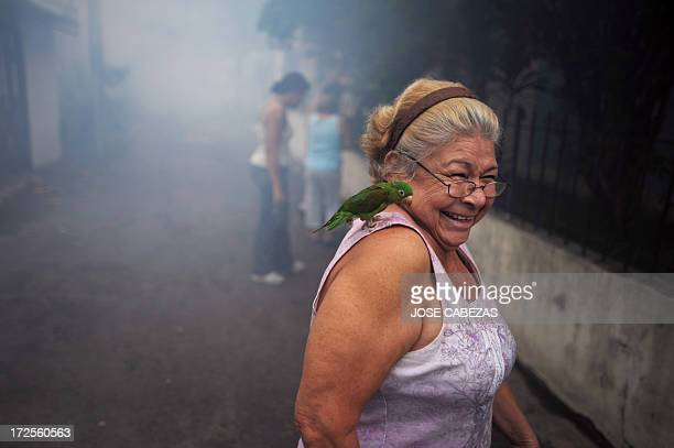 A woman takes her parrot away from where sanitation worker fumigate against the Aedes aegypti mosquito vector of the dengue fever a the 5 de...