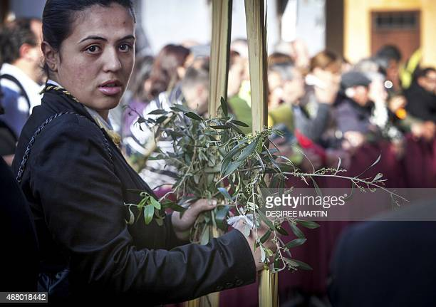 A woman takes holds palm and olive branches blessed during the morning Mass at the Cathedral of San Cristobal de La Laguna during a procession...