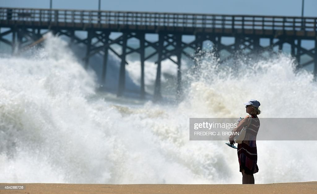 A woman takes in the view as big waves crash ashore beside the pier at Seal Beach, California on August 27, 2014, where some overnight flooding occurred as the surging ocean water resulting from Hurricane Marie almost reached beachfront homes. And as surfers prep for what could be some of the biggest swells of the year, county and city officials are using tractors to fill in sand berms along coastal beaches, in a hopeful effort to avoid any flooding or other damage resulting from Hurricane Marie. AFP PHOTO / Frederic J. BROWN