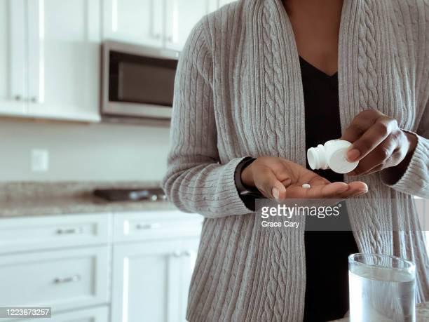 woman takes medication - medicijnen innemen stockfoto's en -beelden