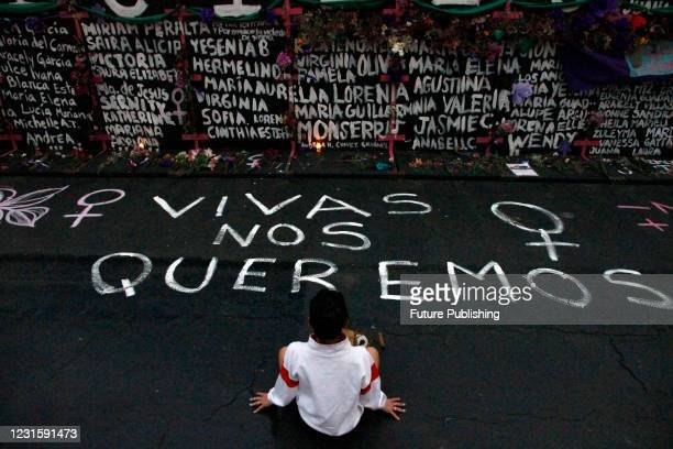Woman, takes part during a performance of Feminist groups, to write names of victims of femicide and place flowers in protest against gender...