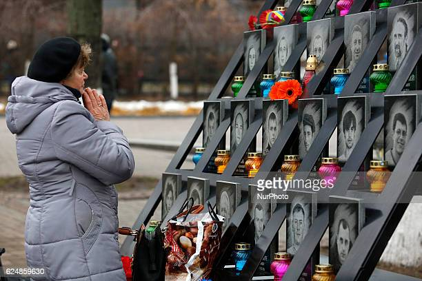 A woman takes part in a commemoration ceremony at the monument to the socalled quotNebesna Sotnyaquot the people killed during the Ukrainian...