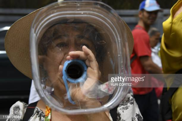 TOPSHOT A woman takes part in a protest against water shortage during the Earth Day at Las Mercedes neighborhood in Caracas on April 22 2019