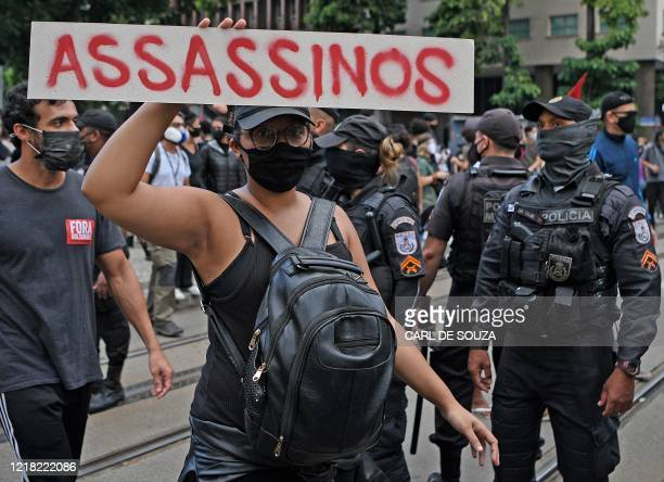 Woman takes part in an anti-racism demonstration in which protesters also shouted slogans against Brazilian President Jair Bolsonaro, in Rio de...