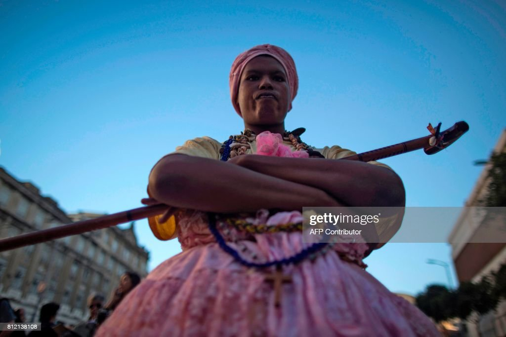 TOPSHOT - A woman takes part in celebrations after Valongo Wharf was added to the list of UNESCO World Heritage sites, in Rio de Janeiro, Brazil on July 10, 2017. The committee of the UN cultural body, meeting in Krakow, Poland, said Valongo was a reminder of an estimated 900,000 African slaves who were brought there by traders starting in 1811. / AFP PHOTO / Mauro PIMENTEL