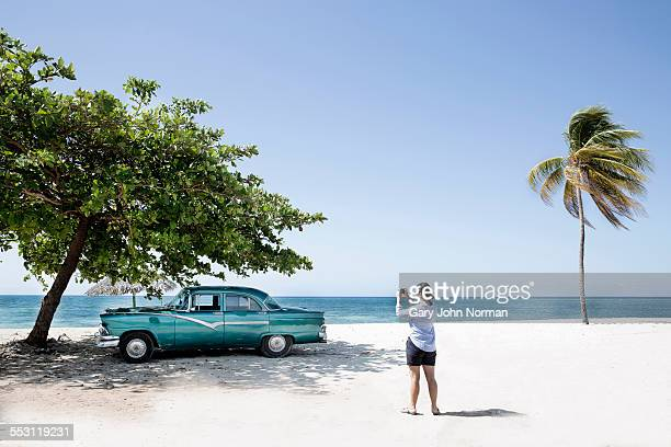 woman takes photo of american car on the beach. - cuba foto e immagini stock
