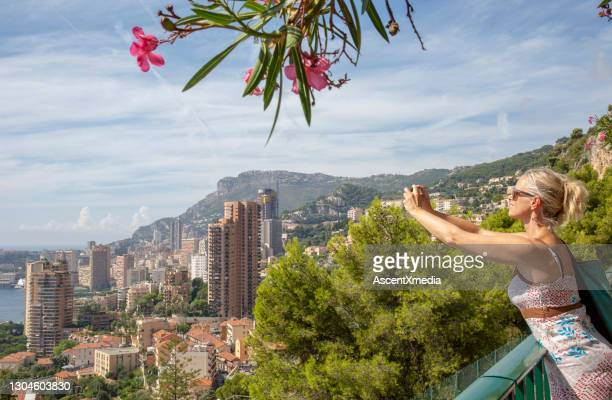 woman takes photo of monaco from elevated walkway - monaco stock pictures, royalty-free photos & images
