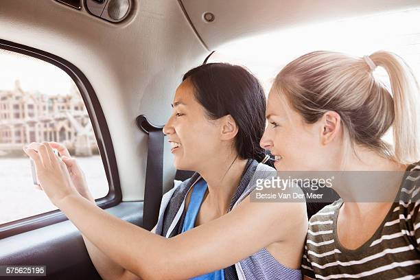 Woman takes photo of out taxi window