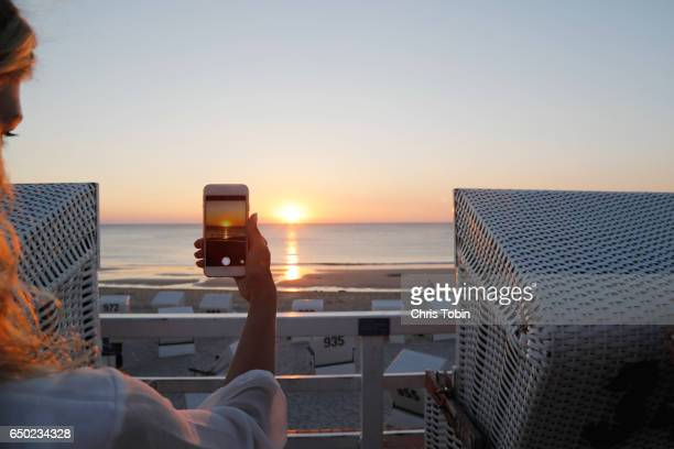 Woman takes photo of sunset on beach