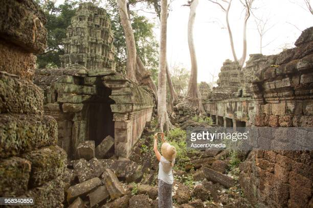 Woman takes photo of temple at Ta Prohm