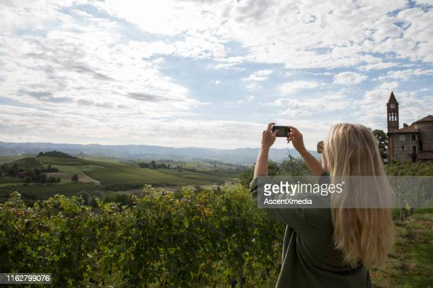 woman takes photo of vineyards near a medieval village - piedmont italy stock pictures, royalty-free photos & images