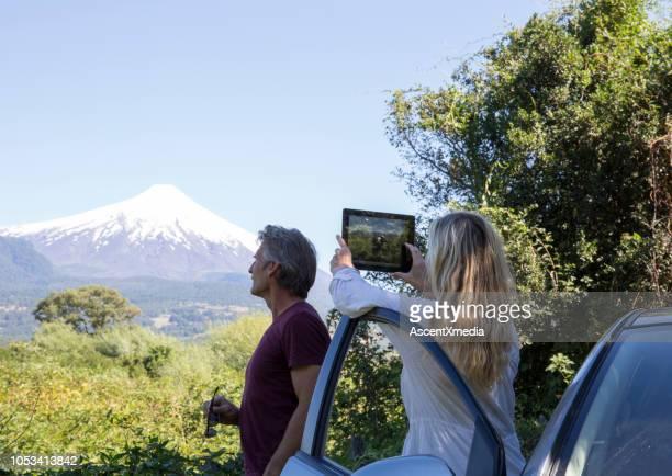 mujer toma foto del volcán con tableta de coche, parece hombre - pucon fotografías e imágenes de stock