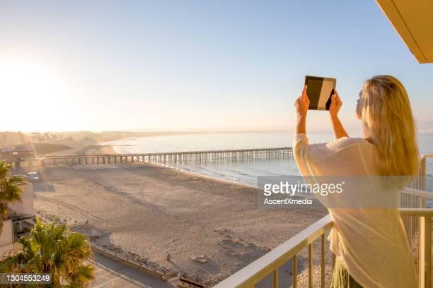 女性は海の上のバルコニーにデジタルタブレットで写真を撮ります - ベンチュラ市 ストックフォトと画像