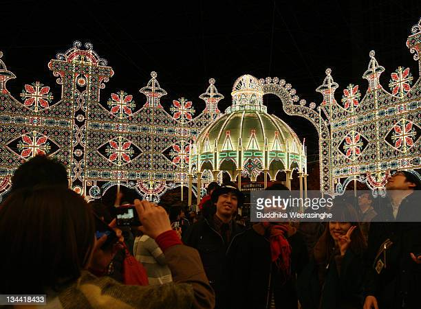 A woman takes photograph her friends during the Kobe Luminarie annual event on December 1 2011 in Kobe Japan The Luminarie festival is held in memory...