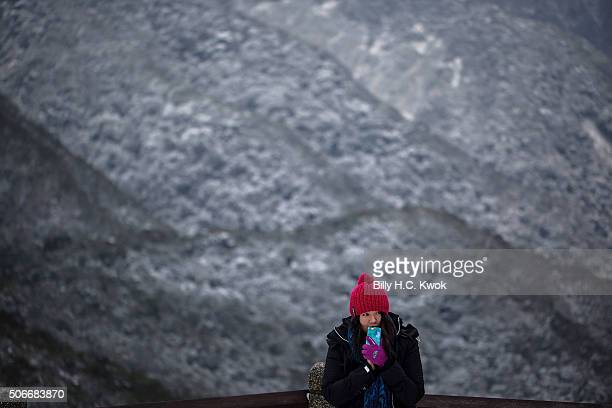 A woman takes photographs as snow is seen at the background on the Yangmungshan National Park during a snowfall on January 25 2016 in Taipei Taiwan...