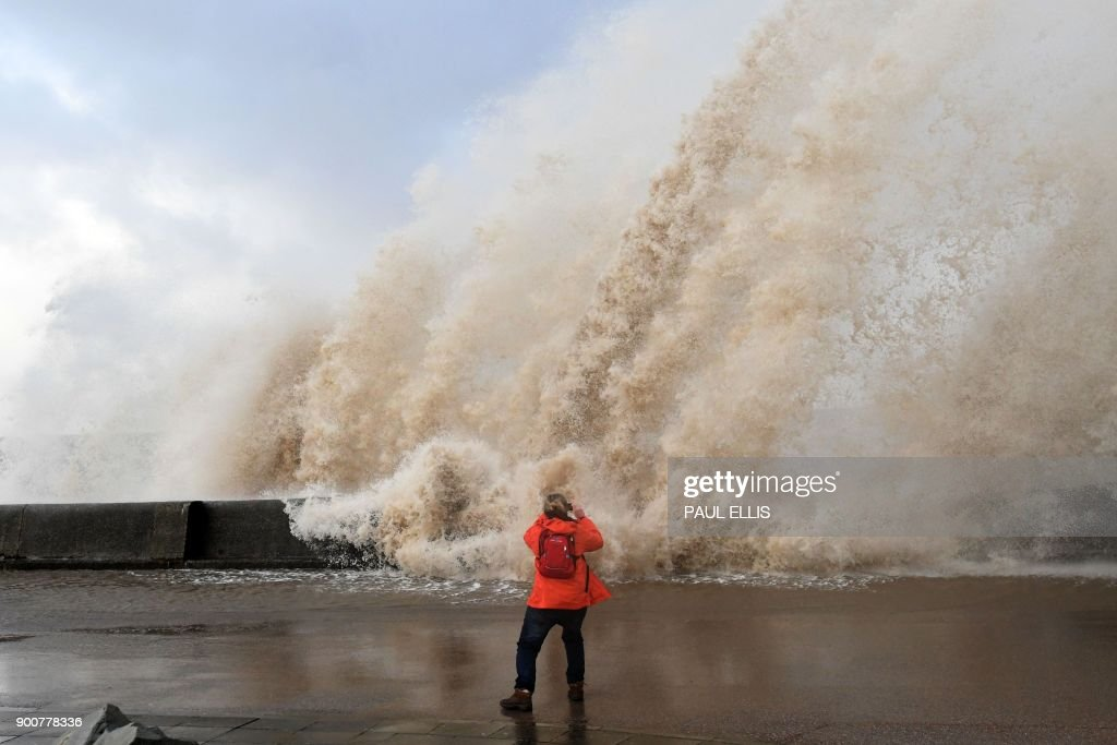 TOPSHOT - A woman takes photographs as waves crash over the tidal wall along the seafront in New Brighton, north west England, on January 3, 2018, as Storm Eleanor swept over the country. Storm Eleanor swept across the country overnight, bringing winds of up to 100 mph in places and carrying rain, hail and thunder and lightning. / AFP PHOTO / Paul ELLIS