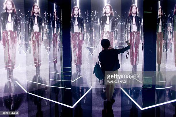 A woman takes photographs of screens showing a fashion show during an exhibition by French luxury brand Louis Vuitton in Beijing on April 9 2015...
