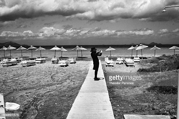 Woman takes photographs of Turkey shores, from the sunbed of a Kos hotel, Greece.