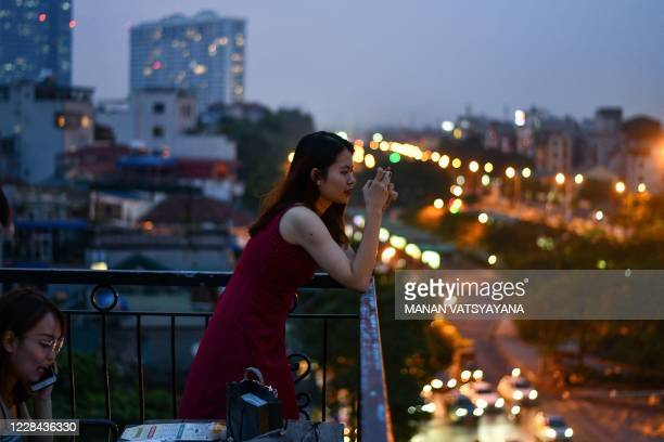 Woman takes photographs on her smartphone from the terrace of a cafe in Hanoi on September 10, 2020.