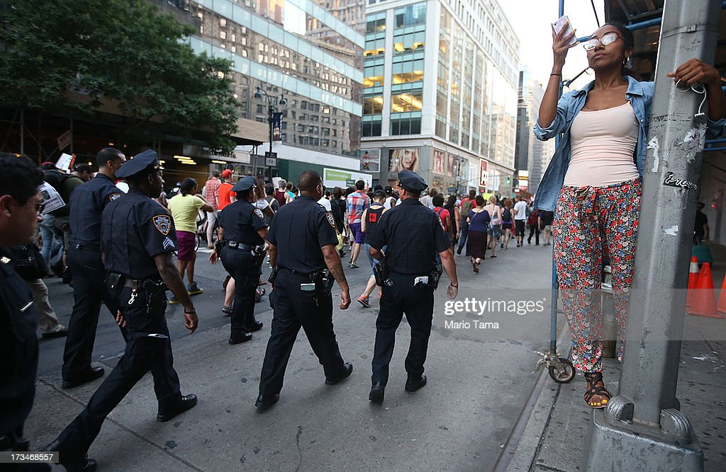 A woman takes photos as people and police walk through the street while blocking traffic after a rally for Trayvon Martin in Union Square in Manhattan on July 14, 2013 in New York City. Many of the marchers made their way to Times Square where they were able to shut down traffic with a rally. George Zimmerman was acquitted of all charges in the shooting death of Martin July 13 and many protesters questioned the verdict.