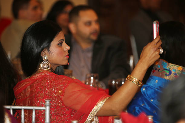 Woman takes photos during a fashion show during the Diwali Gala Celebration in Mississauga Ontario Canada on 25 November 2017 This luxurious gala...
