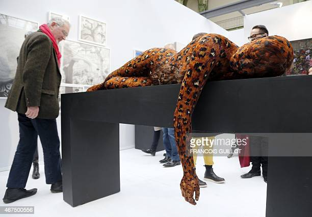 A woman takes photos of a sculpture by British artist Lucy Glendinning entitled 'The girl in her dreams' displayed at the Art Paris Art Fair at the...