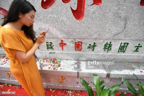 Woman takes photos of a stone tablet that reads blessed land for Chinese football, which is unveiled at Helong Sports Centre Stadium on June 9, 2017...