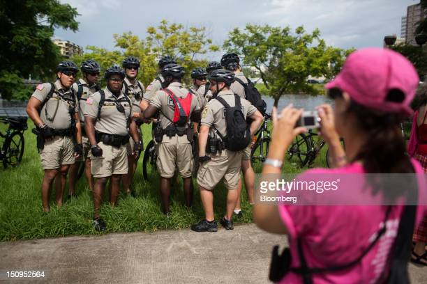 A woman takes photos of police officers at the Planned Parenthood Women Are Watching rally on the third day of the Republican National Convention in...