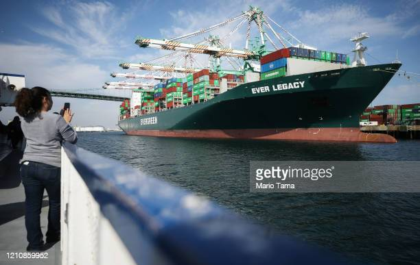Woman takes photos of the container ship Ever Legacy being offloaded after arriving from Taipei at the Port of Los Angeles, which is the nation's...