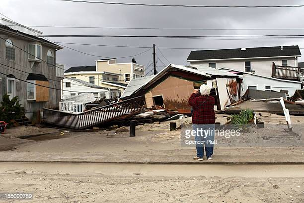 Woman takes photos of the damage after Hurricane Sandy on October 30, 2012 in the Breezy Point neighborhood of the Queens borough of New York City....