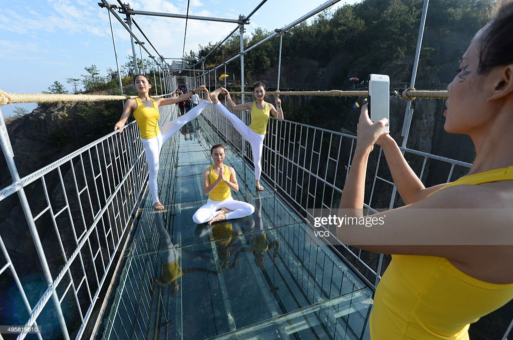 A woman takes photos of yoga enthusiasts practicing on a glass suspension bridge at the Shiniuzhai National Geological Park on November 5, 2015 in Pingjiang County, Yueyang City, Hunan Province of China. 100 yoga enthusiasts practice on the glass suspension bridge with a length of 300 meters and a maximum height of 180 meters at the Shiniuzhai National Geological Park in Pingjiang.