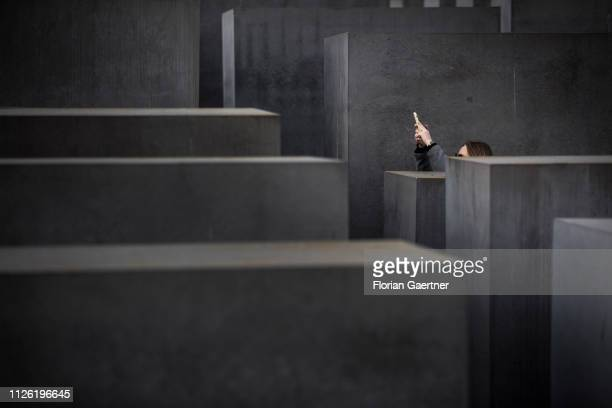 A woman takes photos with her smartphone at the Holocaust Memorial on February 20 2019 in Berlin Germany