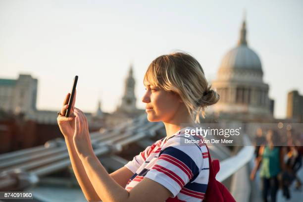 Woman takes photos with smartphone, st Paul's cathedrale in background.