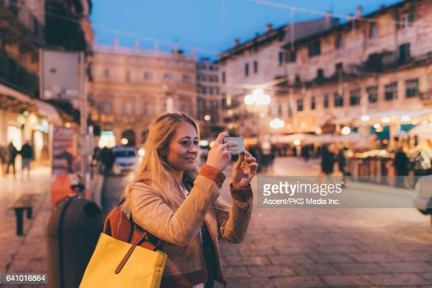 Woman takes pic from urban piazza, twilight
