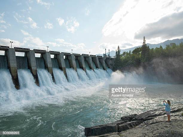 Woman takes pic of water flowing through hydro dam