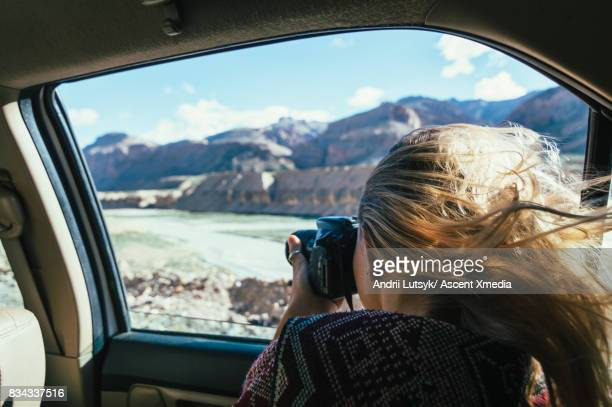 Woman takes pic out car window in mountain landscape