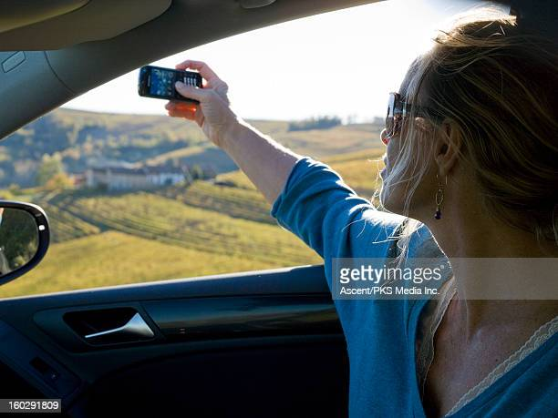 Woman takes picture form car, above vineyards