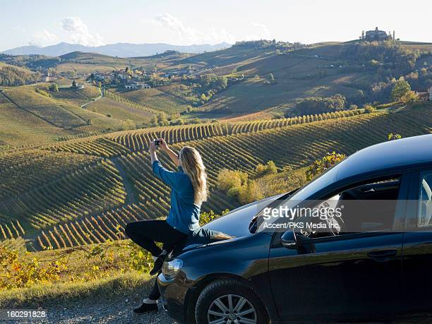 Woman takes picture from car, above vineyards
