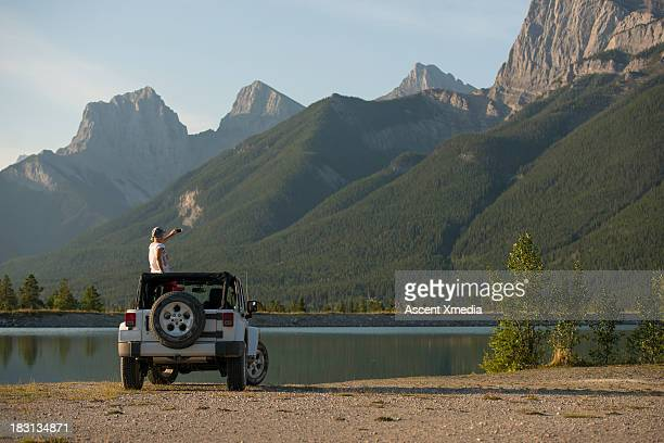 woman takes picture from jeep sunroof, mtn lake - meeroever stockfoto's en -beelden