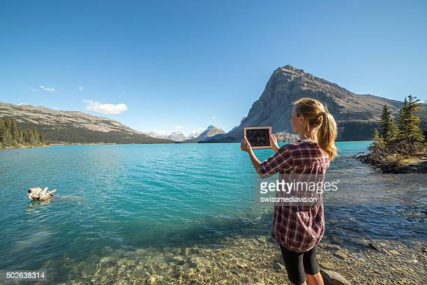 Woman takes picture of mountain lake using digital tablet