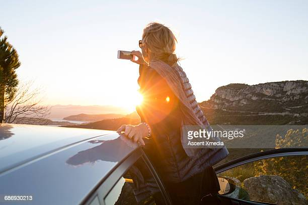 Woman takes picture of sunrise over sea, hills