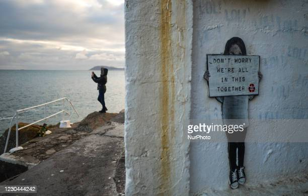 Woman takes picture of the sea next to a shelter with an artworks that reads ' Don't Worry We're All In This Together' seen at the Vico bathing...