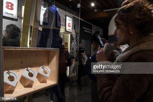 Woman takes picture of the three gold medals won by former French alpine skier Jean-Claude Killy during the 1968's Olympics Winter Games in Grenoble,...