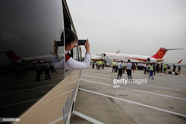 A woman takes pictures as an ARJ21700 China's first domestically produced regional jet arrives at Shanghai Hongqiao Airport after making its first...