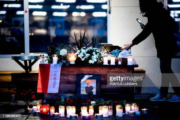 Woman takes pictures at a makeshift memorial for Swedish pop singer and songwriter Marie Fredriksson outside Baggpipe Studios in Skarmabrink,...