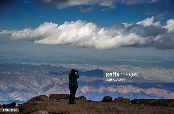 A woman takes pictures at the top of Pikes Peak mountain in the Front Range of the Rocky Mountains within Pike National Forest 10 mi west of Colorado...