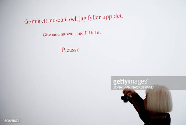 A woman takes pictures during the Picasso/Duchamp 'He was wrong' exhibition at the Moderna Museet in Stockholm on August 23 2012 In the exhibition...