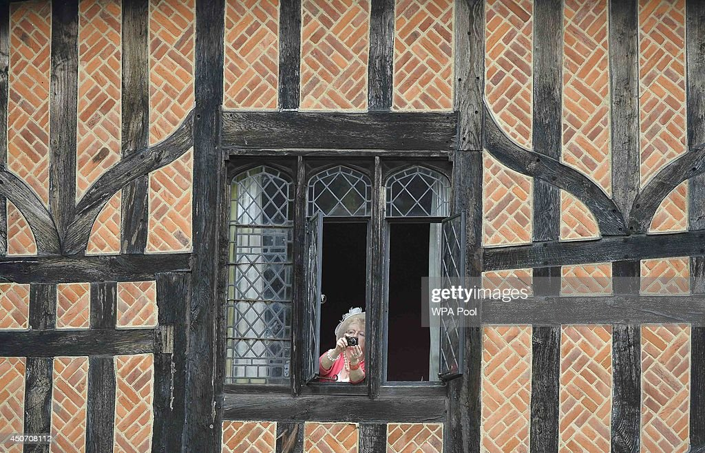 A woman takes pictures from a cottage inside Windsor Castle as Britain's Royal family attend the Most Noble Order of the Garter Ceremony procession on June 16, 2014 in Windsor, England. The Order of the Garter is the senior and oldest British Order of Chivalry, founded by Edward III in 1348. Membership in the order is limited to the sovereign, the Prince of Wales, and no more than twenty-four members.