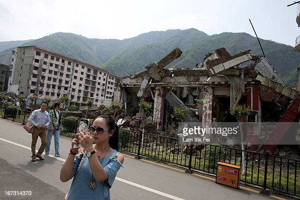 A woman takes pictures in front of a collapsed building at an earthquake memorial park at the Beichuan town in Sichuan province on April 24 2013 in...