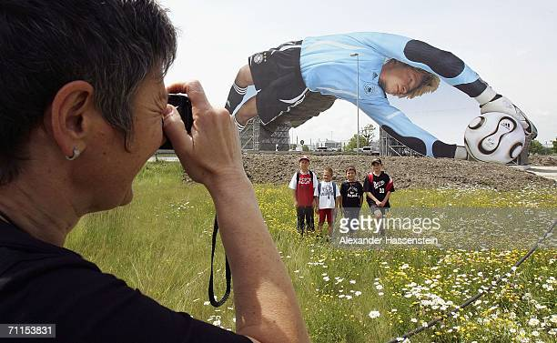 A woman takes pictures in front of a giant poster of German National Goalkeeper Oliver Kahn unveiled at the Munich Airport on June 8 2006 in Munich...